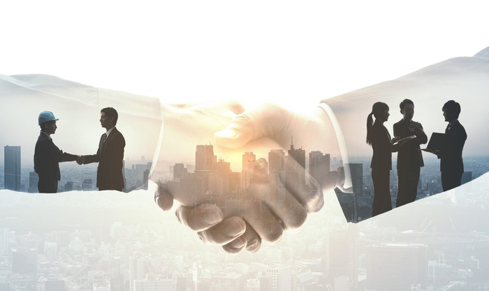 closeup of two hands shaking, with the silhouettes of a construction worker and other executives seen within the sleeves of the arms of the hands in close-up.