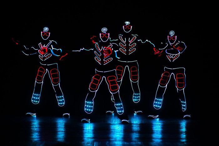 Four glowing figures on a dark stage.