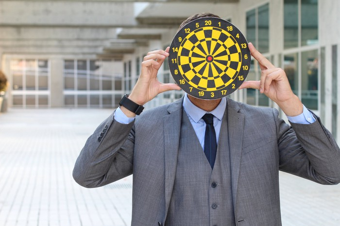 A businessman holds a dartboard in front of his face.