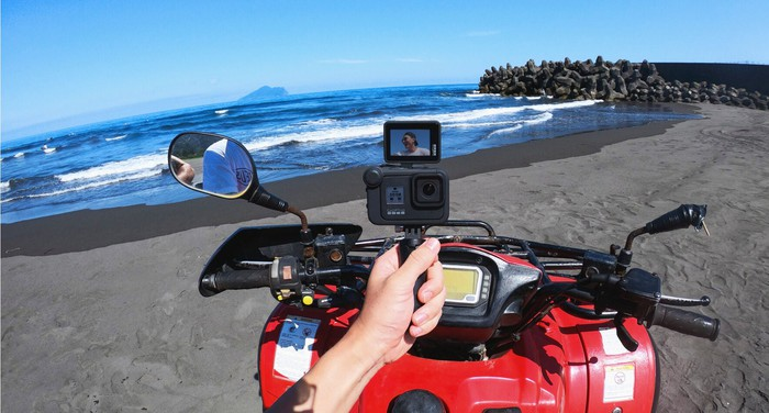 Quad rider holding action camera while at beach