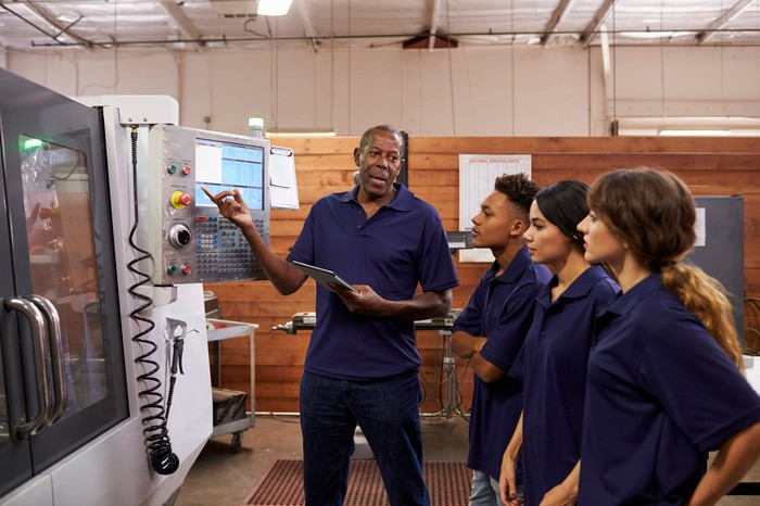 Three younger people watch an older man operate a machine.