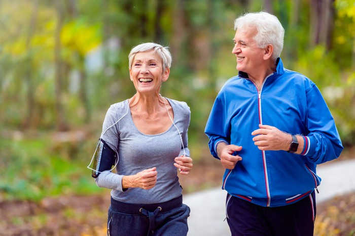 Smiling older man and woman running outdoors