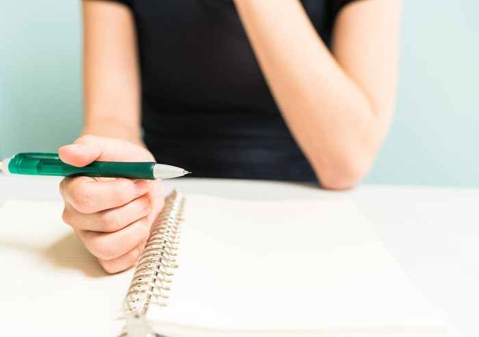 Woman about to take notes on notepad