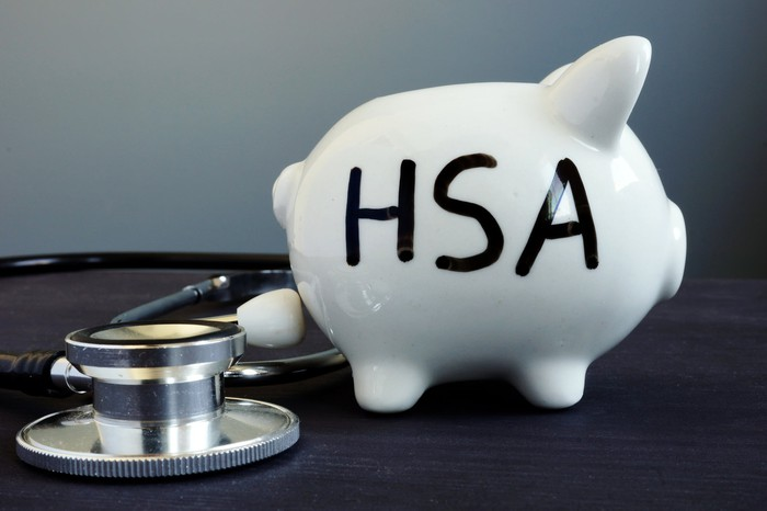 Piggy bank with the letters HSA written on the side next to a stethoscope