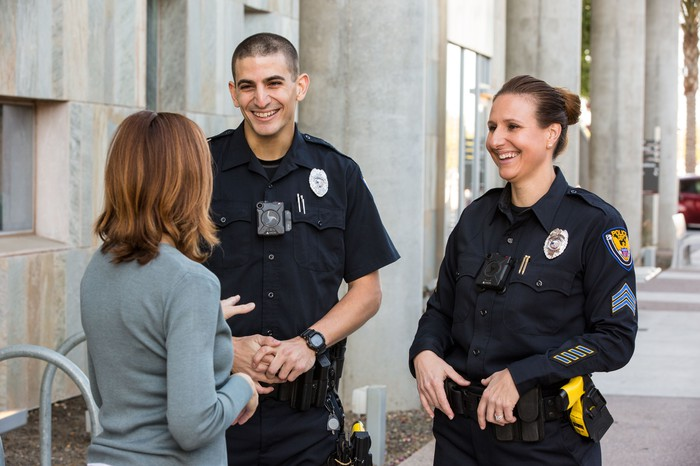 Two police officers with body cameras talk to a civilian.