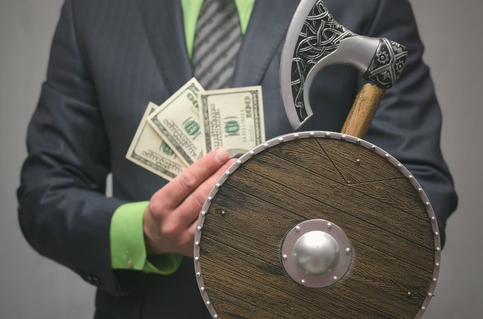 A businessman holding a Viking axe and shield and some money