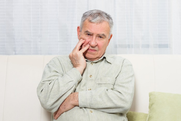 Seated older man holding his face, with a serious look.