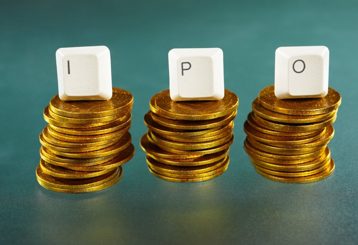 Keyboard letters spelling IPO sit atop separate piles of coins.