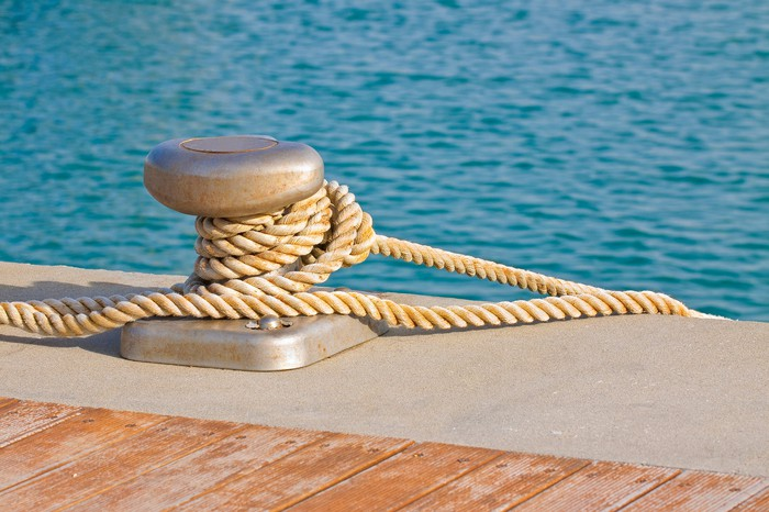 Close-up of a cleat for mooring boats with rope wrapped around it at waters' edge.
