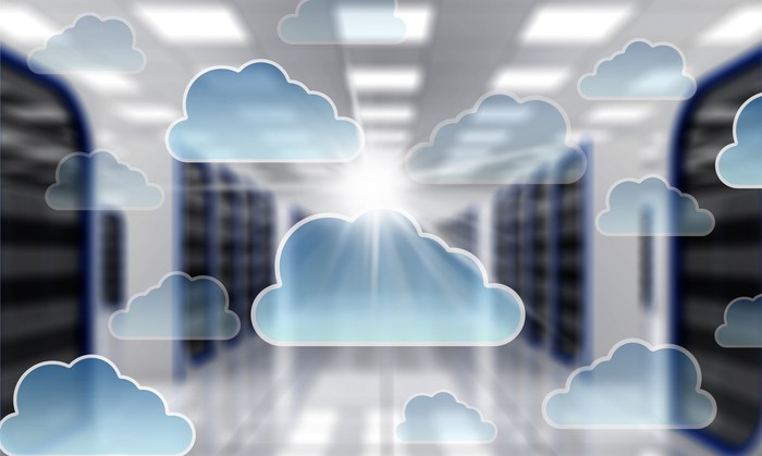 A bank of servers with an overlay of cloud computing emblems.