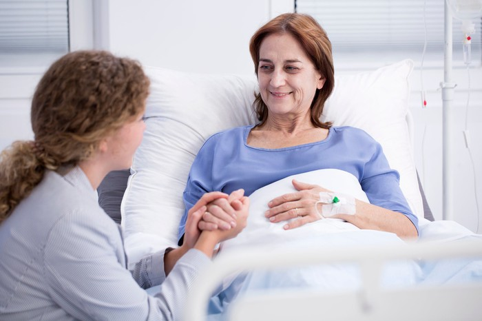 Woman in a hospital bed holding hands with another woman