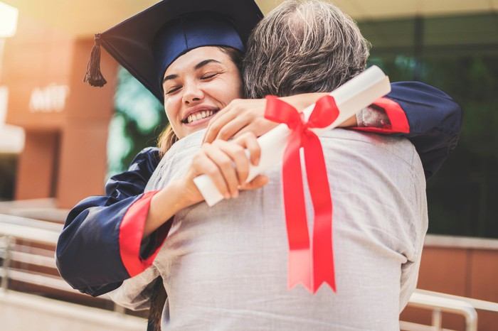 A young woman in a cap and gown holding a diploma hugs an older person.