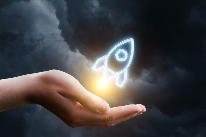 A 2D image of a rocket appearing to take flight from a person's cupped hand, set against a stormy sky.