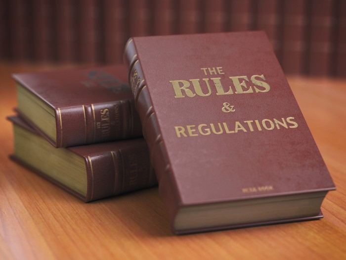 """Photograph of hardback books, one of which has the words """"The Rules & Regulations"""" written on cover"""