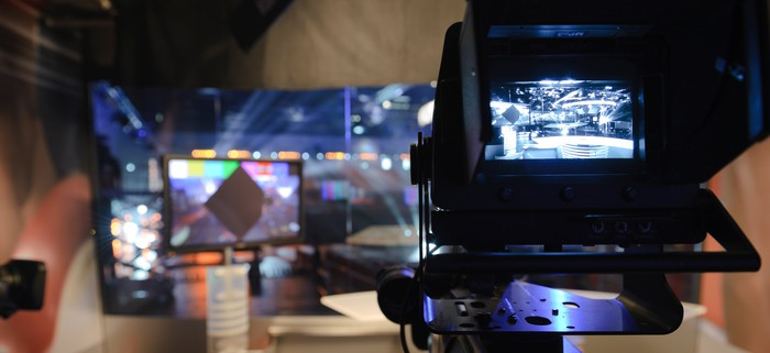 A camera pointed at an empty set inside a television studio.