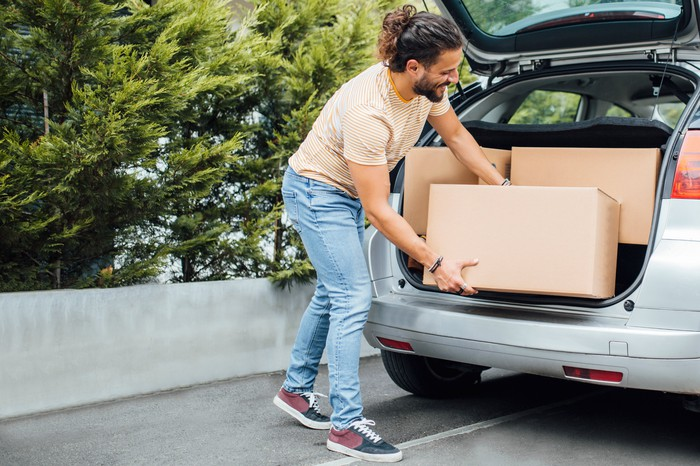 A young man in casual clothes loads large boxes into a hatchback car.