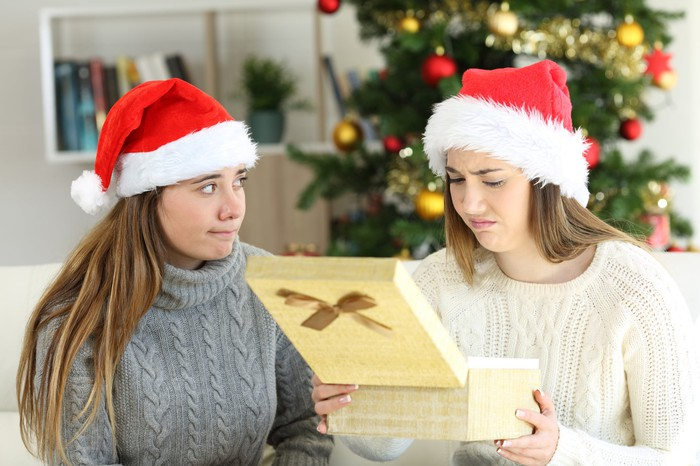 A woman looks unhappy as she opens a gift.