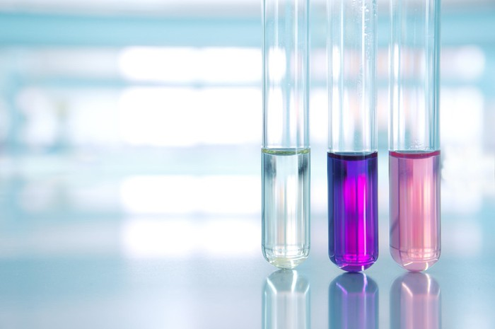Three test tubes half filled with liquids of different colors.