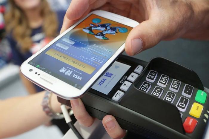 Mobile device held in hand over Visa card reader.