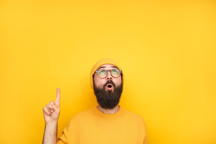 Man in bright yellow sweater and hat looking up and pointing with finger in excitement.