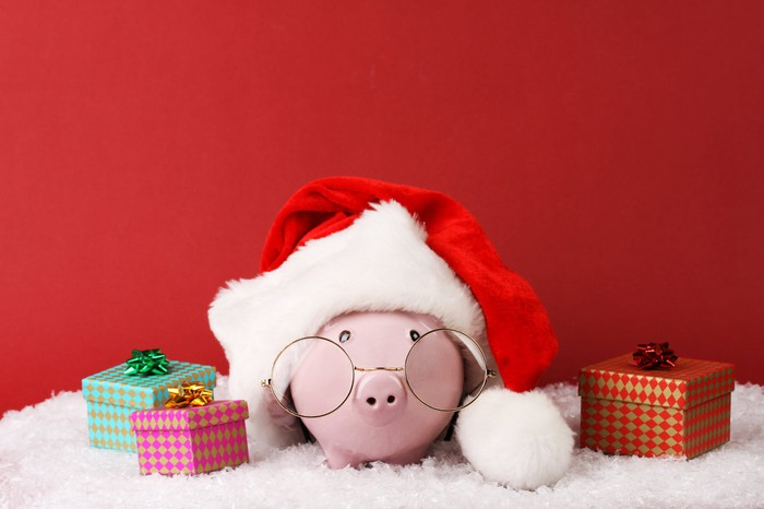 A piggy bank wearing a Santa hat and glasses, surrounded by gifts