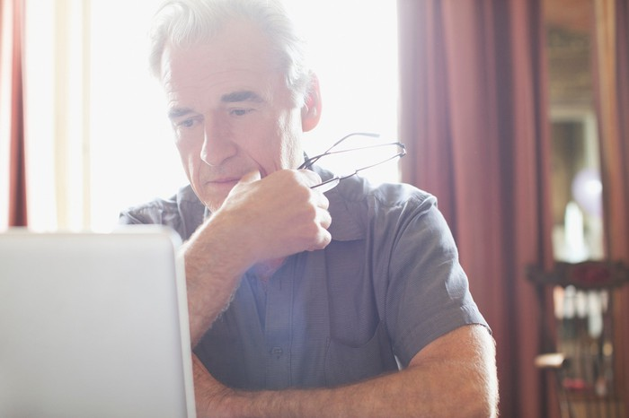 Older man with serious expression sitting at laptop