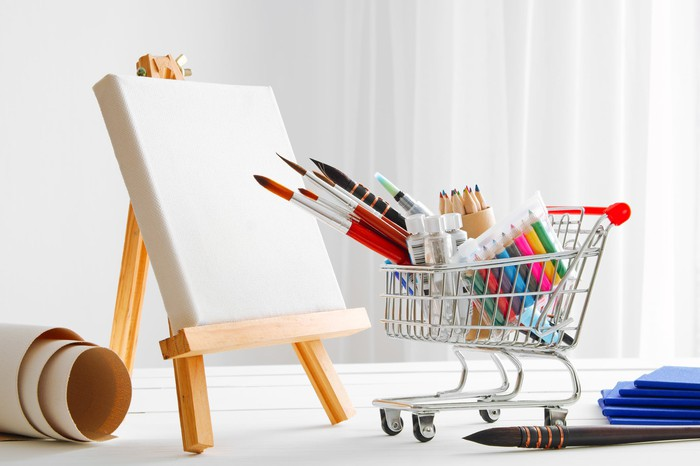 Craft store concept: Miniature shopping cart filled with art supplies beside a miniature easel.