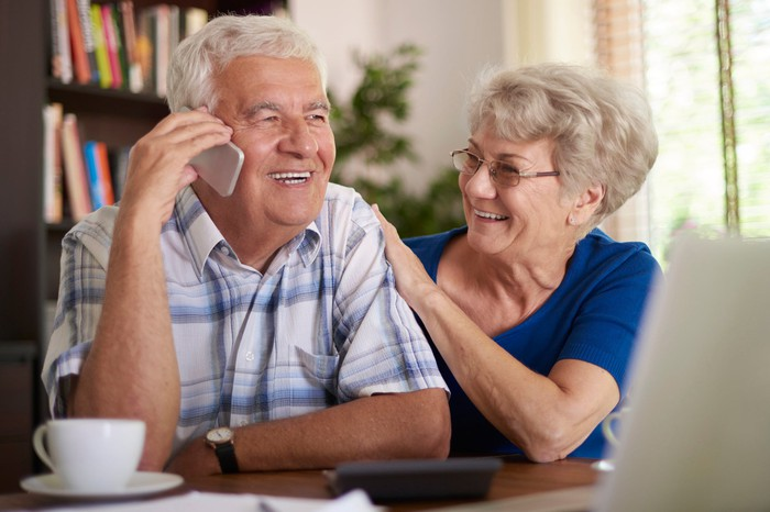 Older woman putting hand on older man's arm while he talks on the phone; both are smiling