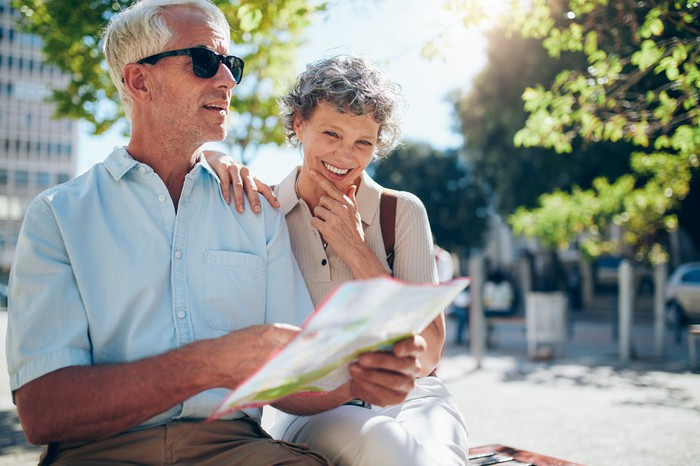 Smiling older man and woman holding a map