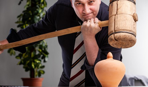 Man holding wooden mallet over pottery urn