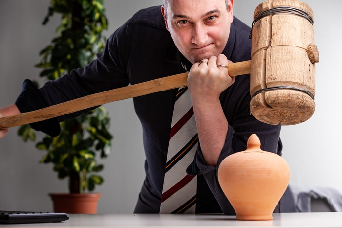 Smirking man in shirt and tie holding a large wooden mallet over a small pottery urn.
