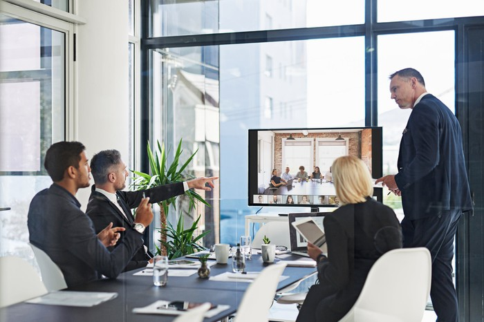 Multiple business people around a conference room table participating in a video conference call.