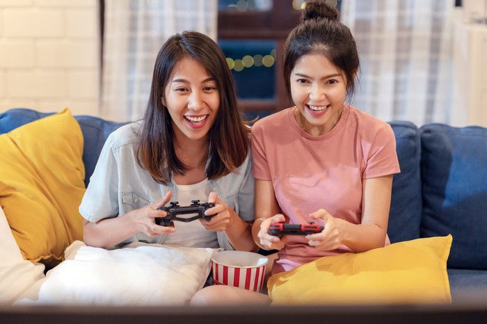 Two Girls Sitting On A Couch Playing a Video Game