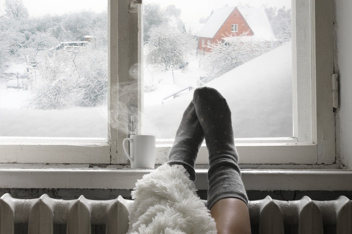 A pair of feet on a radiator in front of a window with snow outside