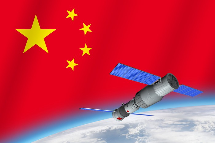 Chinese-flagged space station over Earth against background of Chinese flag