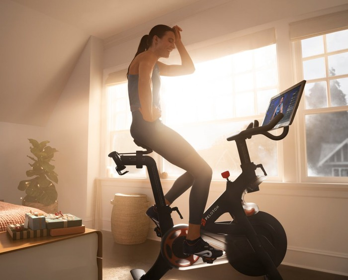 Woman sitting on a Peloton stationary bike