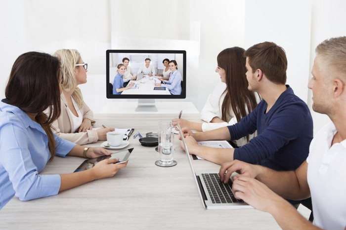 Five employees meeting with five other employees via a Zoom videoconference.