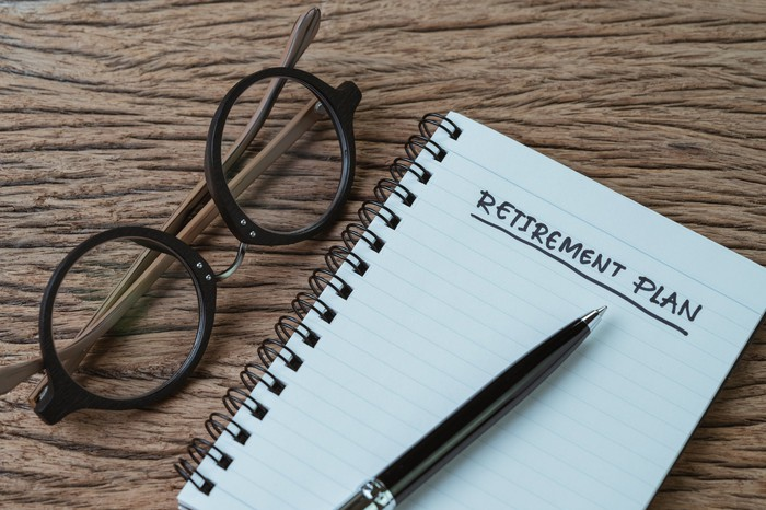 Pen resting on notebook with the words retirement plan written on it; notebook is on a wooden surface next to a pair of eyeglasses