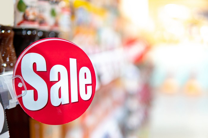 """Close-up of a red and white """"Sale"""" sign in a discount store."""