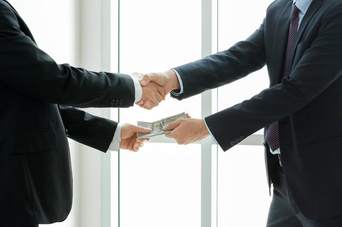 Two men in suits shaking hands, while exchanging money.