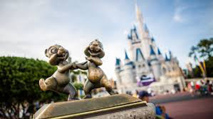 Close-up photo of a bronze statue featuring the chipmunk duo Chip and Dale, with the Cinderella castle from Disney World Tokyo in the background.