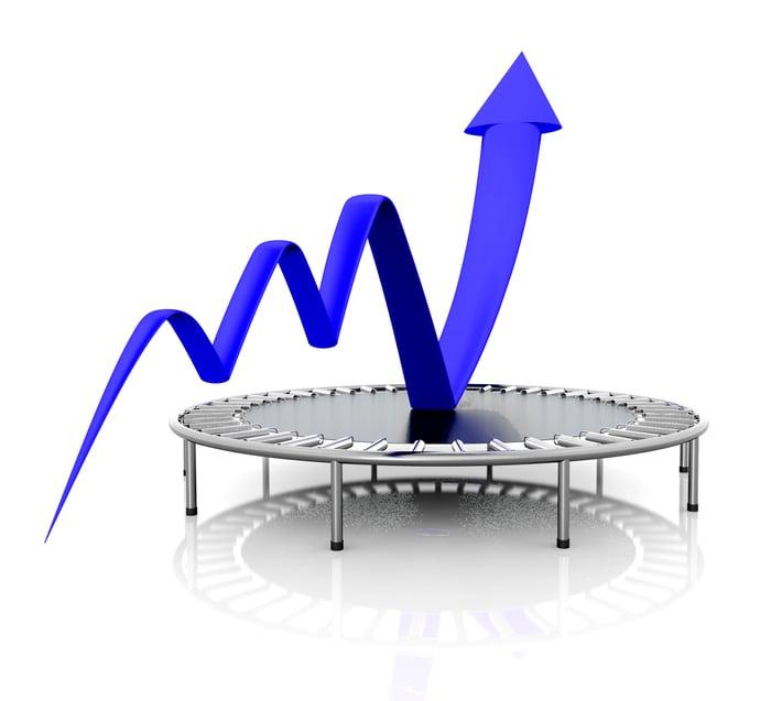 A blue charting arrow bouncing upward from a trampoline.