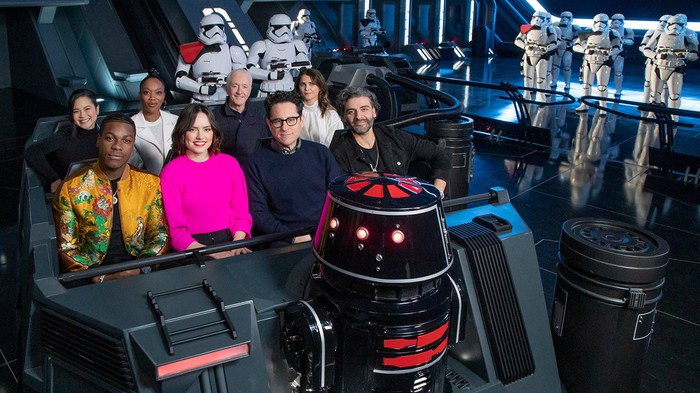 The cast of Star Wars: The Rise of Skywalker enjoying a ride on Rise of the Resistance with Stormtroopers in the background..