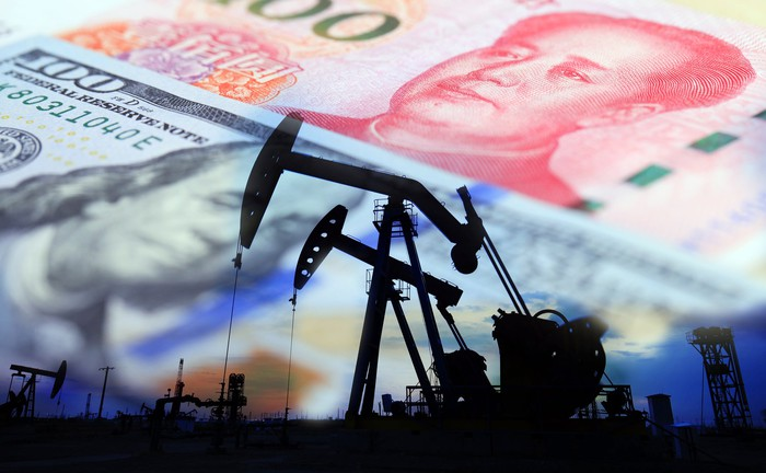 Oil rigs set against a background of a 100-dollar bill and a 100-yuan note.
