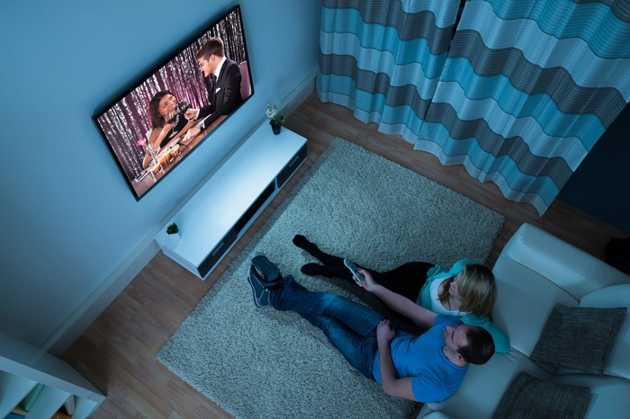 A couple sitting in a darkened living room watching television