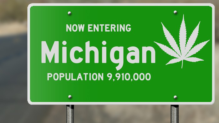 Michigan state sign adorned with cannabis leaf.