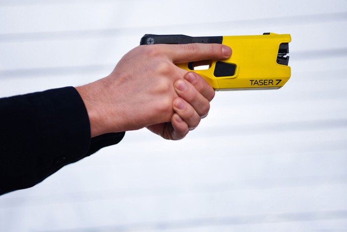 A person holding and aiming an Axon Taser 7