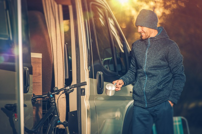 A man holds a cup of coffee and smiles outside his RV camper.