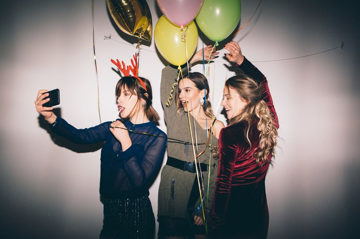 Three girls take a selfie with balloons at a party.