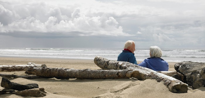 Two people with white hair sitting among driftwood on a beach.